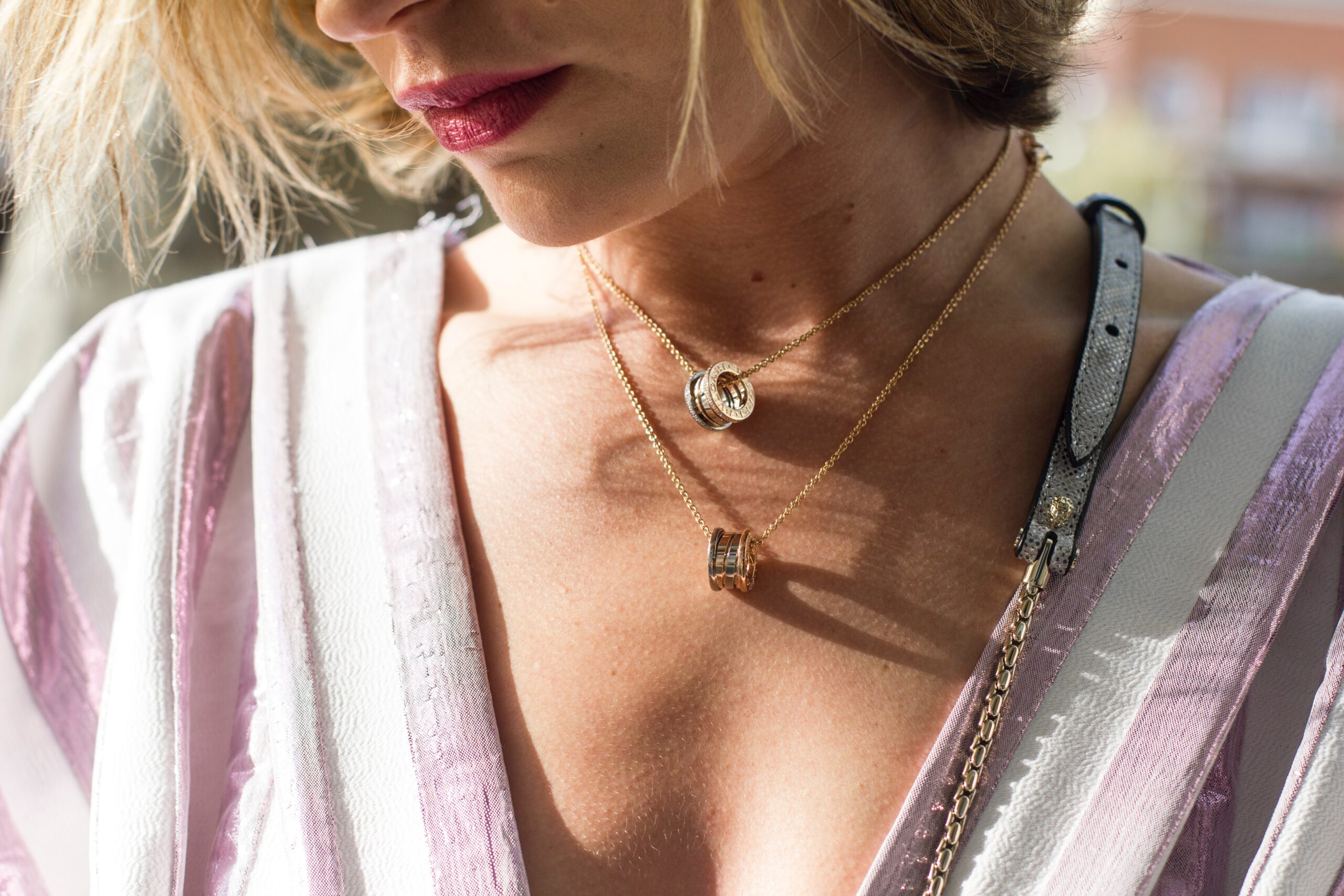 woman wearing gold-colored ring pendant necklaces